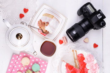 Different sweets and photo camera on table top view