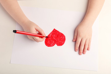 Close-up of child hands drawing a red heart