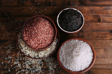 Different kinds of rice in bowls on wooden background