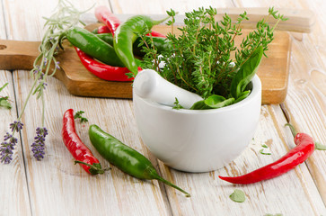 Fresh herbs and  chili peppers on a wooden background.