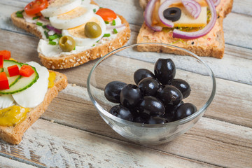 Bowl of blueberries and sandwiches on wooden background