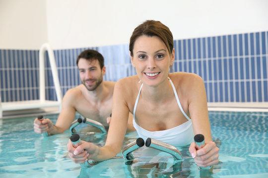 Couple in pool doing aquabike training