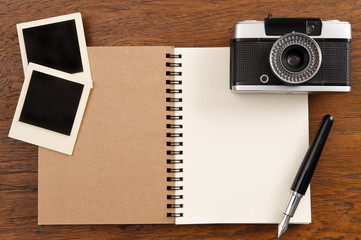 Blank notebook with pen, photo frames and camera