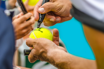 Tennis player signs autograph after win