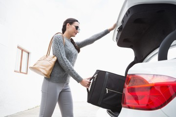 Woman pulling out a baggage of her car trunk