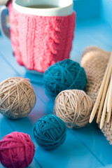 Bright balls of yarn, wooden knitting needles, knitted blanket l