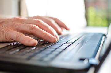 Hand typing on a laptop
