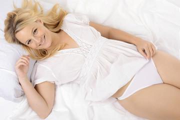 Frau im Nachthemd liegt auf weißer Bettwäsche