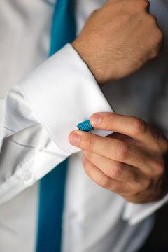 Man's hands closeup fixing his blue cufflinks