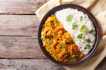 Shrimps curry with rice on a plate. horizontal view from above