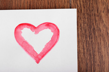 Painted heart shape on sheet of paper on wooden table