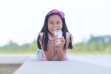 Little girl drinking milk with a milk mustache