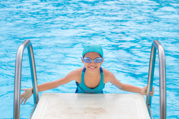 Little girl in swimming pool. Summer outdoor