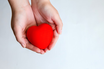 Woman's hands holding sweet red heart