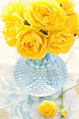 beautiful flowers. yellow roses in a blue vase on the table.