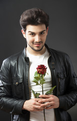Handsome man with a single red rose