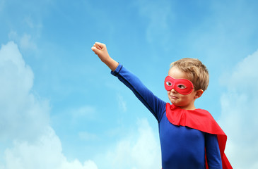 Boy in red superhero cape and mask