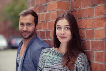 attraktives junges paar lehnt an backstein-mauer