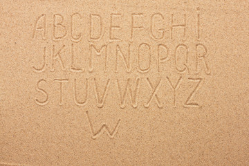 English, German, Portuguese alphabet  written on the sand