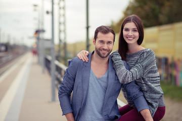 glückliches paar wartet am bahnsteig