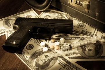 Gun,syringe and pills on dollar bills.