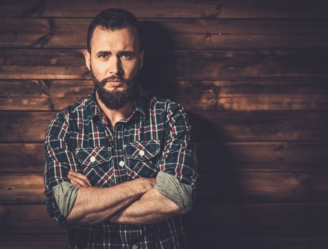 Man wearing checkered shirt in wooden rural house