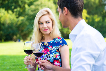 Paar trinkt Rotwein im Gras in Sommer Park