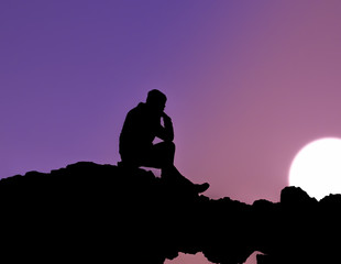 Silhouette of man sitting at sunset