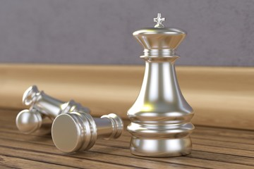 Silver chess pieces on wooden floor