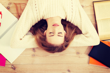 Beautiful woman lying on the floor with books.