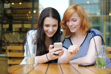 Two young girls using smart phone
