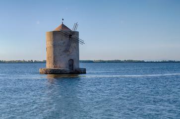 Old windmill in a lagoon at sunset. Orbetello, Argentario, Italy