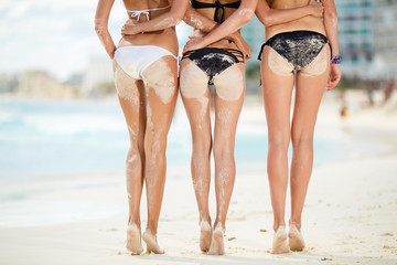 Three sexy women's butt in the sand on the beach.