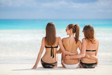 Girls in bikinis sunbathing, sitting on the beach