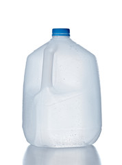 Plastic jug, recyclable and reusable bottle jug container for water, milk and other liquids with no tag and drops on the surface, isolated on white background with reflection