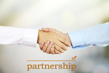 Business handshake symbolizing partnership on light background