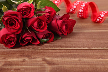 Valentine background of  red roses and ribbon on wood. Space for
