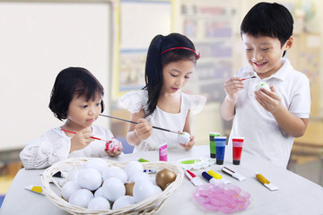 Children painting eggs
