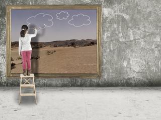 Mädchen malt Wolken in ein Bild