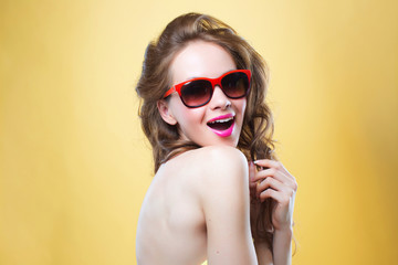 woman wearing sunglasses on gold background