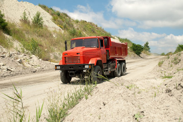 Red dump truck driving on a road in a stone quarry