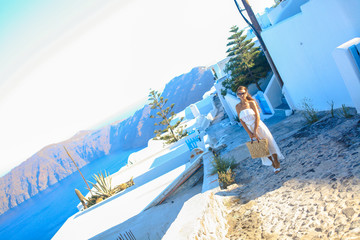 Young woman in famous capital Fira of Santorini, Greece