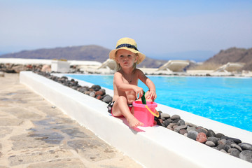Adorable little girl near pool during greek vacation in