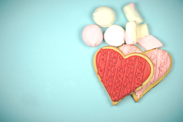 A pair of heart-shaped biscuits and some marshmallow on a light