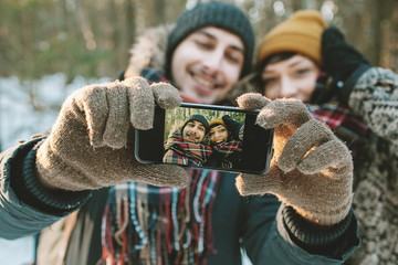 Couple making selfie in winter forest