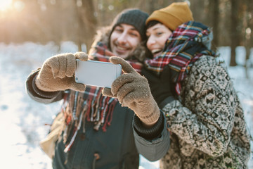 Couple making selfie in winter forest