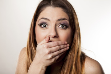 Ashamed young woman covering her mouth with her hand