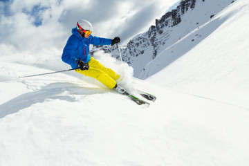 Male skier on downhill freeride with sun and mountain view