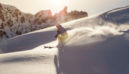 Fototapete - Male skier on downhill freeride with sun and mountain view