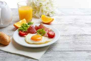 Bacon and eggs on wooden table and white background